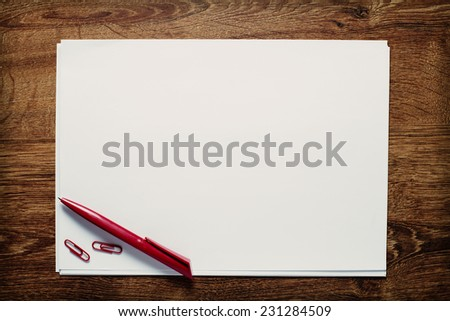 Red ballpoint pen and paperclips lying on a stack of blank sheets or pages of white paper with copyspace for your text on a wooden desk, view from above