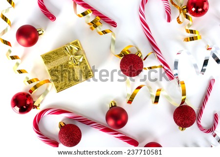 red balls, bright bows, gold gift box and candy-cane on white surface, top view - stock photo