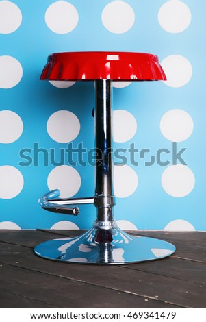 Red bar stool against a background of wall
