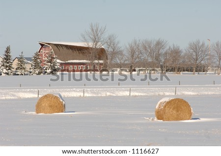 Red Barn and Bales of Hay on Farmland - stock photo