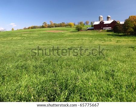 Red Barn and Silo with a green grass field in the foreground - stock photo