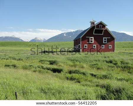 Red barn in a large green field with mountains in the distance