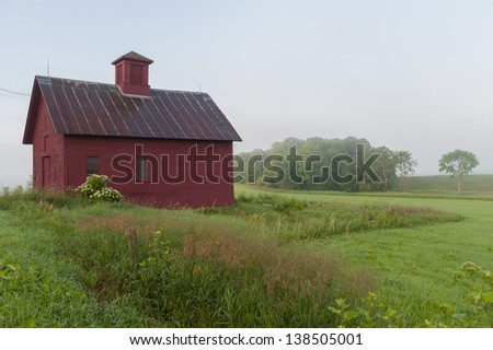 Red barn in early morning mist, Stowe, Vermont, USA - stock photo