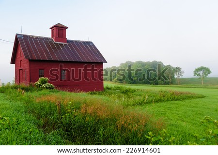 Red barn in the early morning mist, Stowe, Vermont, USA. - stock photo