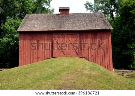 Red barn with doors on grassy hill