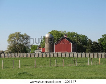 red barn with silo on fenced land