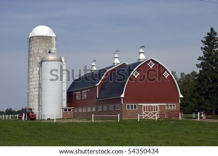 red barn with silos and tractor on a dairy farm - stock photo