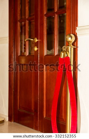Red barrier rope on wooden door background. Selective focus. event object