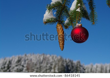 red bauble christmas ball ornament outside in a snowy winter scene - stock photo