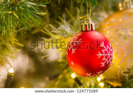 Red Bauble hanging Down From a Branch of a Christmas Tree. Shallow Depth of Field