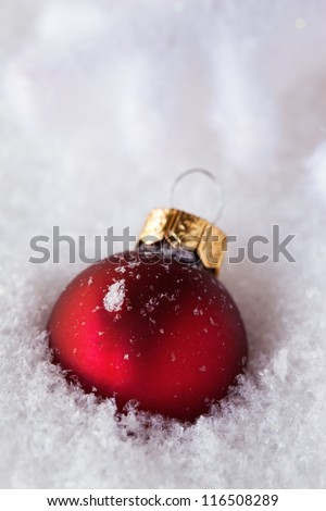 red bauble in snow - christmas card - stock photo
