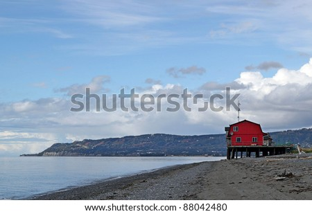 Red beach house on the Kachemak bay in summer with interesting clouds and blue sky. - stock photo