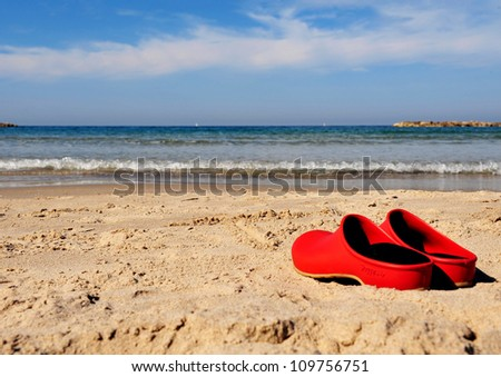 Red beach shoes left on the send in Tel-Aviv beach on the coastline of the Mediterranean sea. Israel. - stock photo