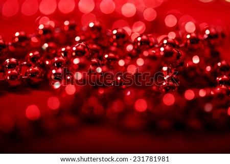 red beads with blurred lights bokeh for Christmas atmosphere holiday background  - stock photo