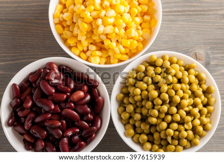 Red beans, green peas and sweet corn in white bowls, closeup, top view, selective focus - stock photo