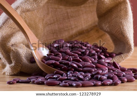 Red beans in a wooden spoon and bag - stock photo