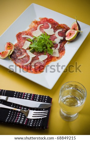 Red beef carpaccio in a white plate with salad, fig fruit, parmesan cheese and olive oil. Yellow background and shallow depth of field. - stock photo