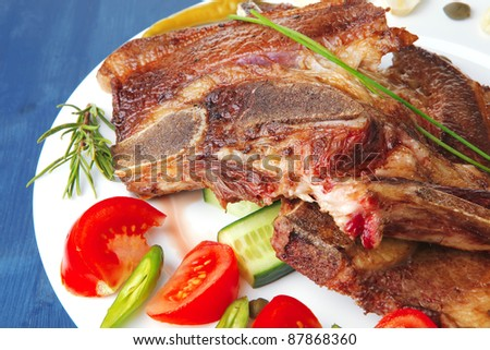 red beef meat steak on white plate with green hot pepper and tomatoes over blue wood table