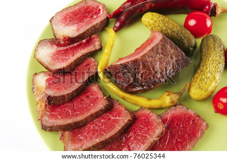 red beef slices on green dish with peppers - stock photo
