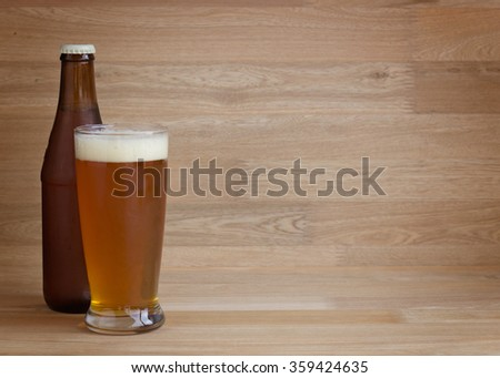 Red beer on glass and beer bottle on wood