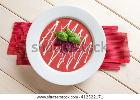 Red beetroot cream soup with pieces of beet and onion