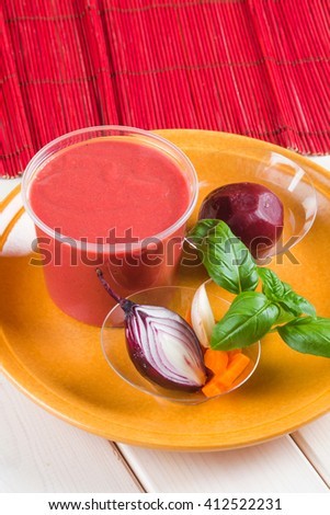 Red beetroot cream soup with pieces of beet and onion on brown ceramic plate - stock photo