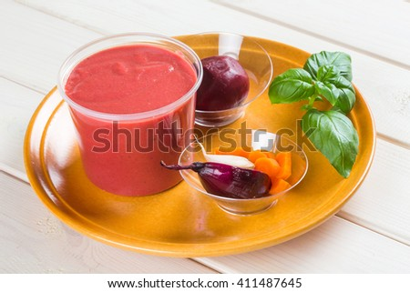 Red beetroot cream soup with pieces of beet and onion on brown clay plate - stock photo