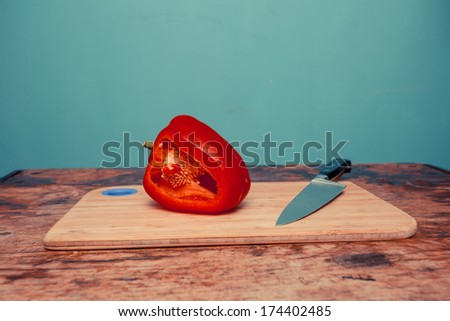 Red bell pepper and knife on chopping board - stock photo