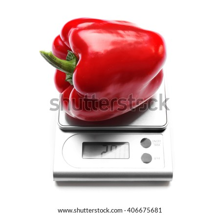 Red bell pepper on digital kitchen scales, isolated on white - stock photo