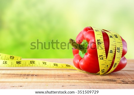 Red bell pepper with yellow measuring tape.