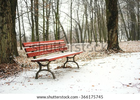 Red bench in the park covered with snow in winter - stock photo