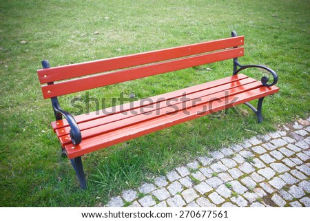 Red bench in the park on green grass. - stock photo