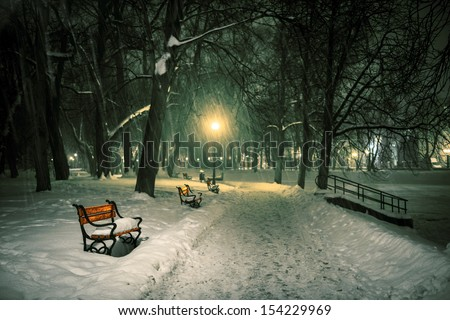 Red bench in the park with falling snow at night