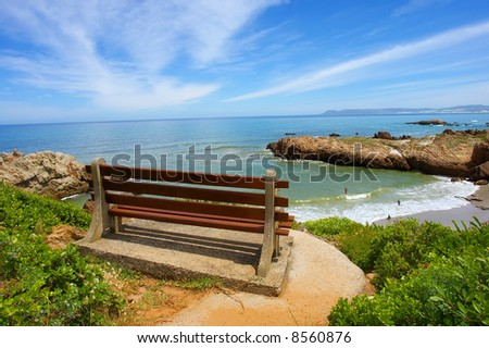 Red bench on cliff rocks next to majestic sea. Shot on Cliff Path near Hermanus, Walker Bay, Western Cape, South Africa. - stock photo