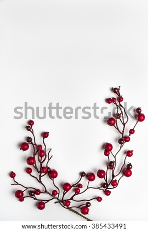 Red berries holly on white. Red Christmas ornaments frame. Image of Christmas. Top view with copy space. - stock photo