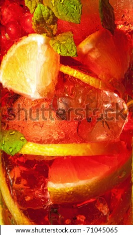 Red berries in a colorful cocktail drink in macro closeup