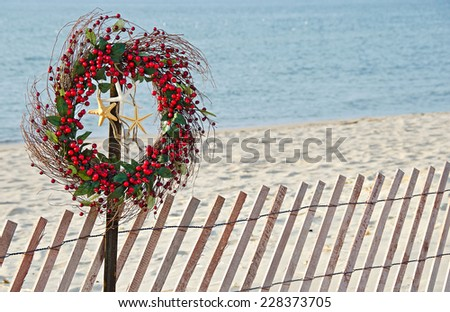 red berry Christmas wreath with starfish on a fence post at the seashore - stock photo