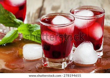 Red berry juice with ice in the shape of hearts, selective focus - stock photo
