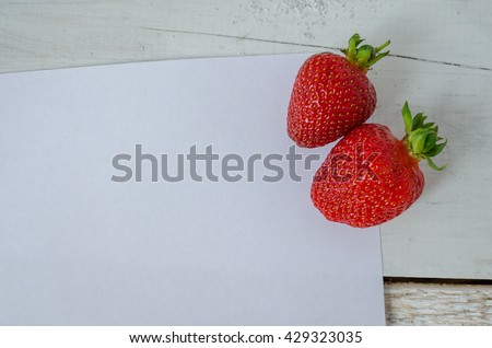 Red berry strawberry on white wooden background with sheet of paper. Background from freshly harvested strawberries with space for text. Strawberry background. Directly above. Top view. Copy space. - stock photo
