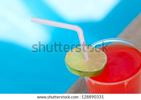 Red Beverage with Straw and Lime beside the pool