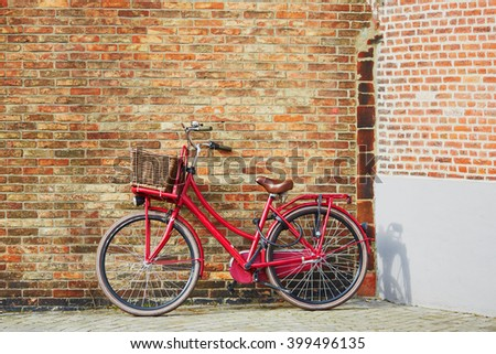 Red bicycle against brick wall in Brugge, Belgium - stock photo