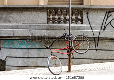 Red bicycle chained to a post in an urban setting - stock photo