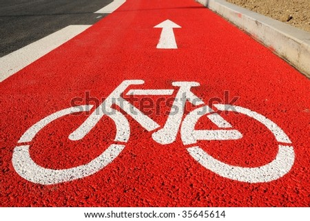 Red bicycle lane with white bicycle sign - stock photo