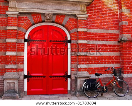 Red bicycle near a red brick wall and a red door - stock photo