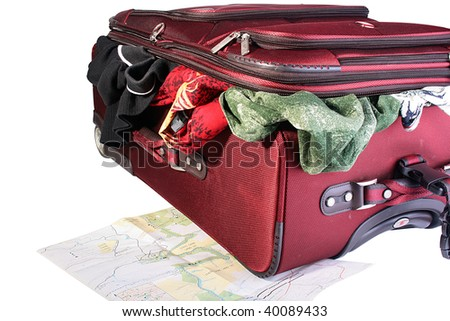 Red big suitcase with things sticking out of it. A suitcase in the course of packing. Under a suitcase the developed card of travel lies. - stock photo