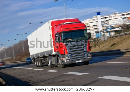 Red big truck driving fast on a high way - stock photo