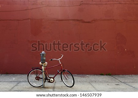 Red biked locked to a parking meter in front of a red painted wall - stock photo