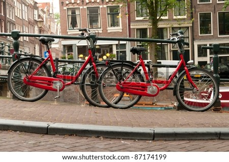 Red bikes parked on a street in Amsterdam, Netherlands - stock photo
