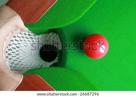 red billiard ball  in front of corner pocket on green baize table - stock photo