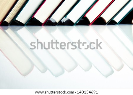 Red, black and green books in a row on white reflective surface - stock photo